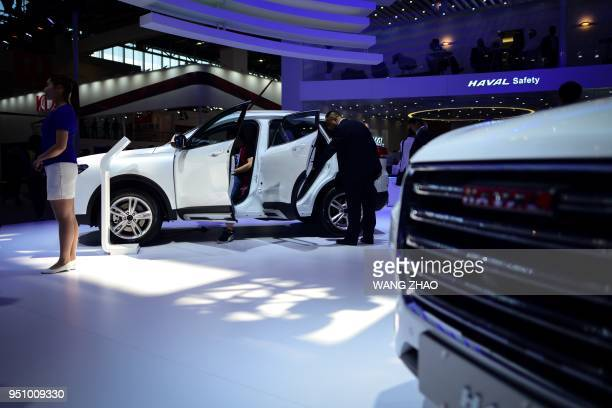 Visitors look at a Haval H4 car on display at the Beijing Auto Show on April 25 2018 Global carmakers touted their latest electric and SUV models in...