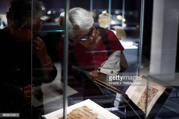 "Visitors look at a historical book during the exhibition ""Savants et croyants, les Juifs d'Europe du Nord au Moyen-Age"" at the Museum of Antiquities..."