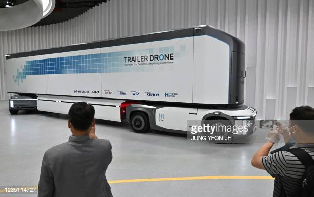 Visitors look at a hydrogen fuel-cell powered trailer drone at the Hyundai booth during a 'Hydrogen Mobility Energy Show' at the Kintex exhibition...