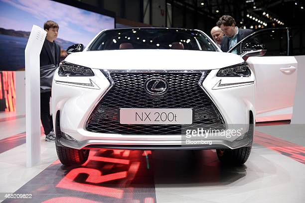 Visitors look at a Lexus NX 200t automobile produced by Toyota Motor Corp as it stands on display on day two of the 85th Geneva International Motor...