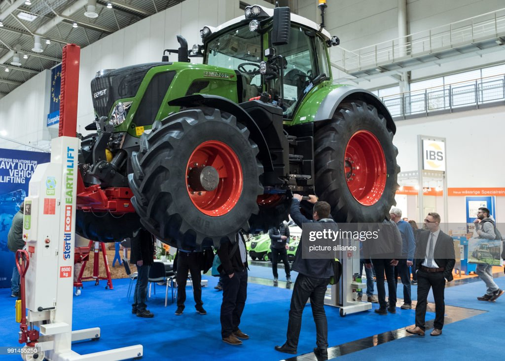 visitors look at a lifting platform for tractors by the company