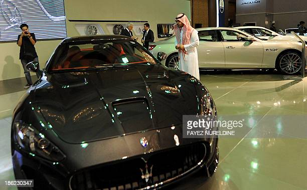 Visitors look at a Maserati car during the 2013 International Luxury Motor Show in the capital Riyadh on October 29 2013 AFP PHOTO/FAYEZ NURELDINE