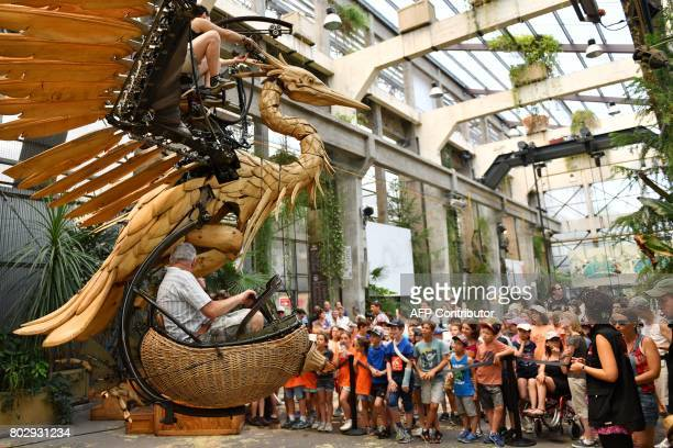 Visitors look at a mechanical heron made of wood and steel at the Machine Gallery of 'Les Machines de L'Ile' in Nantes western France on June 20 2017...