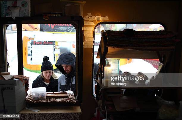 Visitors look at a menu displayed outside a food truck in the Hirafu area of Kutchan Hokkaido Japan on Saturday Feb 14 2015 Japan had a record number...