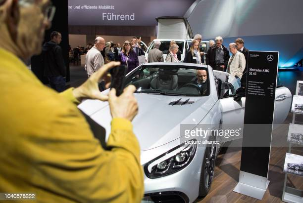 Visitors look at a MercedesAMG SL 63 at the shareholders' meeting of German car manufacturer Daimler in Berlin Germany 06 April 2016 Following a...