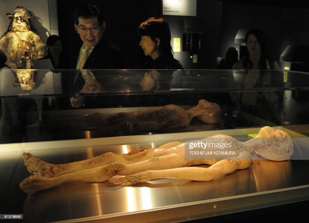 Visitors look at a model depicting the 1947 Alien Autopsy in Roswell, New Mexico during the 'The Science of Aliens' exhibition at the Miraikan, the National Museum of Emerging Science and Innovation in Tokyo on June 3, 2008. The three-month-long exhibition which will end on June 16 attracted more than 100,000 visitors.