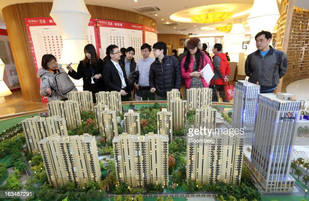 Visitors look at a model of residential buildings at the Fun City apartment complex developed by China Vanke Co in a showroom in Beijing China on...