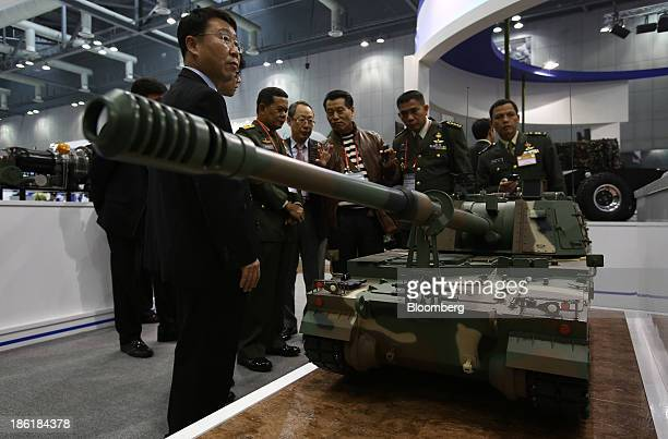 Visitors look at a model of the Samsung Techwin Co. K-9 tank at the Seoul International Aerospace & Defense Exhibition 2013 in Goyang, South Korea,...