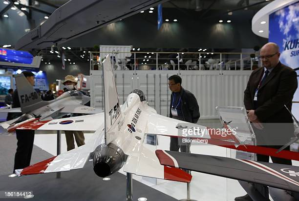 Visitors look at a model of the T-50 trainer jet, developed by Korea Aerospace Industries Ltd. And Lockheed Martin Corp., at the Seoul International...