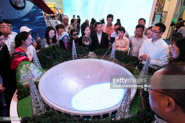 Visitors look at a model world's largest 500meter Aperture Spherical Telescope which is located in Guizhou province at a special exhibition...