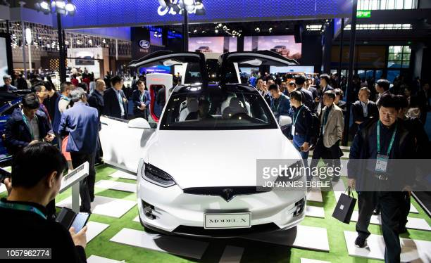 Visitors look at a Model X car of electriccarmaker Tesla Motors at the first China International Import Expo in Shanghai on November 6 2018