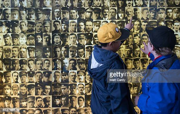 Visitors look at a montage of pictures of missing servicemen displayed at the Thiepval Memorial to the Missing of the Somme on May 18, 2016 near...