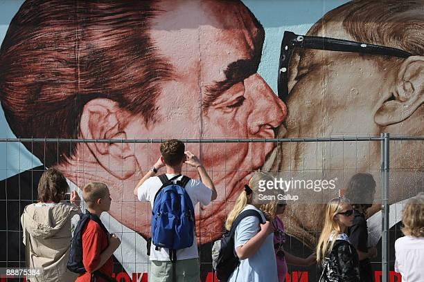 Visitors look at a mural by Russian artist Dmitry Vrubel that shows former Soviet leader Leonid Brezhnev kissing former communist East German leader...