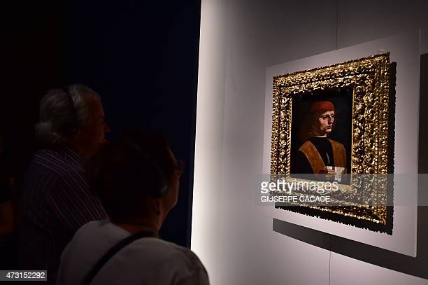 Visitors look at a painting entitled Portrait of Musician as part of the exhibition Leonardo Da Vinci at the Palazzo Reale museum on May 13 2015 in...