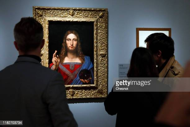 Visitors look at a painting entitled 'Salvator Mundi' by School of Leonardo da Vinci during a press visit of the exhibition Leonardo da Vinci at the...