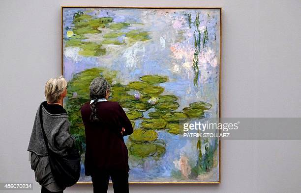 Visitors look at a painting Nympheas by French painter Claude Monet displayed in the exhibition 'Monet Gauguin van Gogh Inspiration Japan' at the...