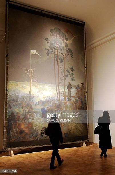 Visitors look at a painting of Czech Art Nouveau artist Alfons Mucha during the opening of the Alfons Mucha exhibition on February 11, 2009 at the...