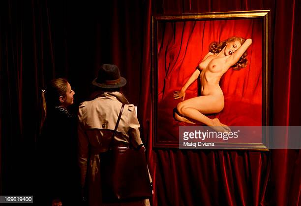 Visitors look at a photo of Marilyn Monroe taken by Tom Kelley in 1949 displayed at the 'Marilyn' exhibition at Prague Castle on May 29 2013 in...