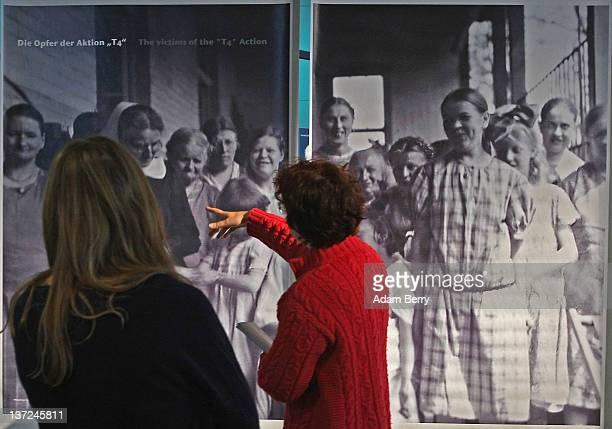 Visitors look at a photo of victims of the 'Aktion T4' Project the policy leading to extermination of the disabled during the Holocaust in the 'In...