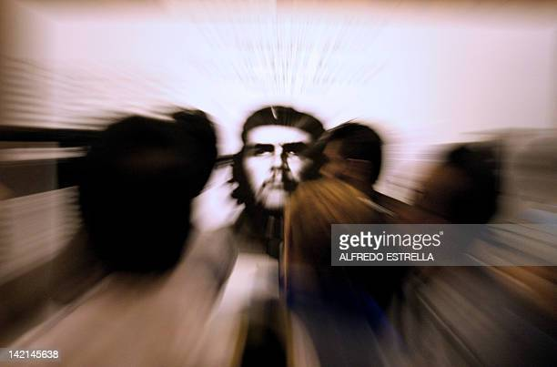 Visitors look at a picture of Argentine born Cuban guerrilla leader Ernesto Che Guevara during the exhibition The Image of Ernesto Che Guevara...