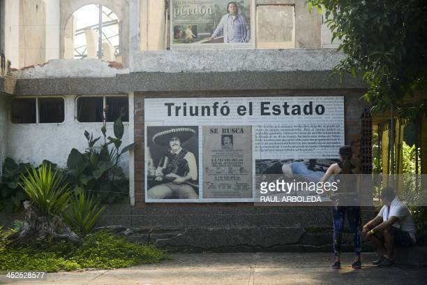 Visitors look at a poster at Colombian drug trafficker Pablo Escobar's damaged mansion at the Napoles Ranch theme park in the Puerto Triunfo...