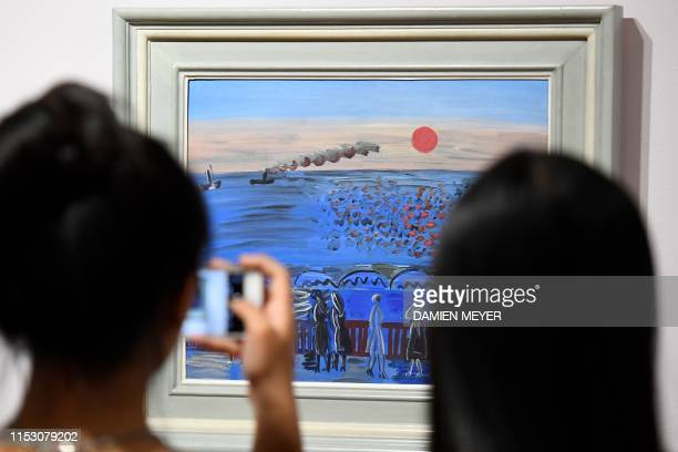 Visitors look at a Raoul Dufy painting Vue de la terrasse de SainteAdresse soleil couchant at the MuMa Andre Malraux Museum of Modern Art in Le Havre...