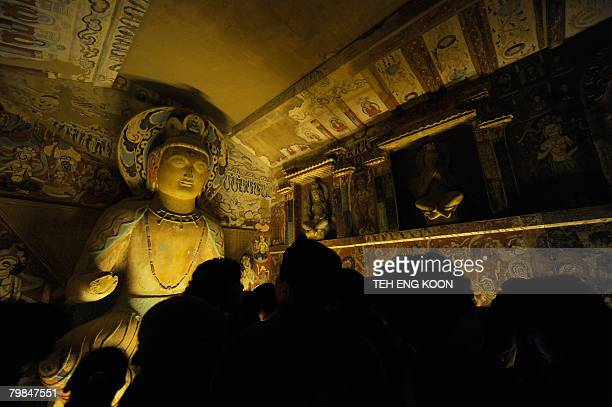 Visitors look at a replica statue of the Buddha from the Mogao Cave during the Dunhuang Art Exhibition in Beijing on February 20 2008 The exhibition...