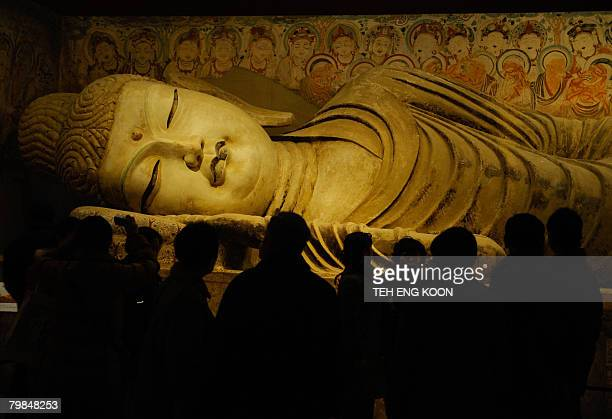 Visitors look at a replica statue of the Sleeping Buddha from the Mogao Cave during the Dunhuang Art Exhibition in Beijing on February 20 2008 The...