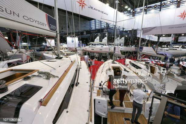 Visitors look at a sailing boat of the French yacht manufacturer Jeanneau during the Paris International Boat Show on December 9 2018 at the Porte de...