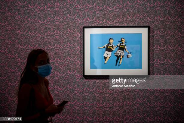 Visitors look at a screen print on paper Jack and Jill by British artist Banksy during the Banksy's Visual Protest Exhibition at the Chiostro del...