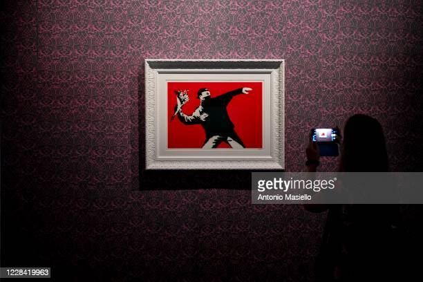 Visitors look at a screen print on paper Love Is in the Air by British artist Banksy during the Banksy's Visual Protest Exhibition at the Chiostro...
