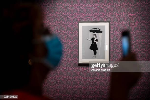 Visitors look at a screen print on paper Nola by British artist Banksy during the Banksy's Visual Protest Exhibition at the Chiostro del Bramante on...