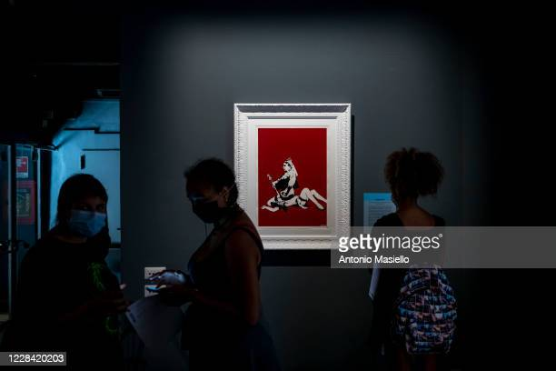 Visitors look at a screen print on paper Queen Vic by British artist Banksy during the Banksy's Visual Protest Exhibition at the Chiostro del...