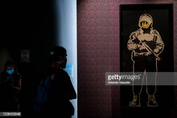 Visitors look at a screen print on paper Smiling cop by British artist Banksy during the Banksy's Visual Protest Exhibition at the Chiostro del...