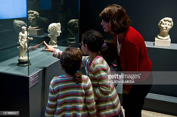 Visitors look at a sculpture displayed at the exhibition Rome The Life and Emperors at the Art Museum of Sao Paulo on January 28 in Sao Paulo Brazil...