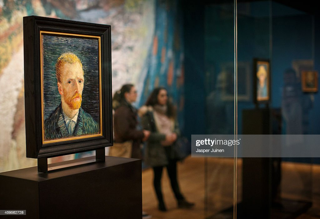 Visitors look at a self portraits of Dutch Post-Impressionist painter Vincent van Gogh on the ground floor of the Vincent van Gogh museum on November 25, 2014 in Amsterdam, Netherlands. The new presentation of the permanent collection of Vincent van Gogh (1853-1890) works focuses on the development of the artist and the myths surrounding Van Gogh's suicide, illness and ear are discussed in detail for the first time at the museum. On the ground floor of the museum, visitor's first walk through an array of the Dutch artist's self-portraits.