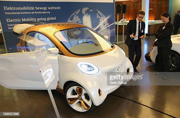 Visitors look at a Smart electric car at the ElectroMobility Conference at the Berlin Congress Center on May 27 2013 in Berlin Germany The...