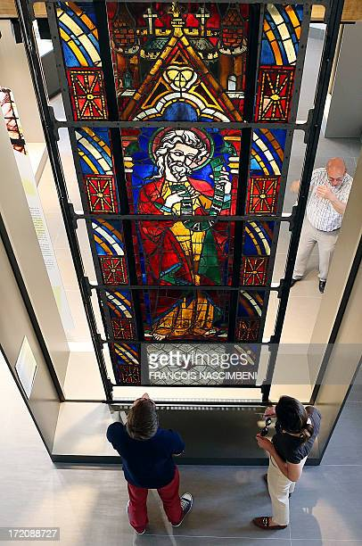 """Visitors look at a stained-glass window entitled """"Le prophete Zacharie"""" and dated from 1270, on July 1 during the permanent exhibition at """"La Cité du..."""
