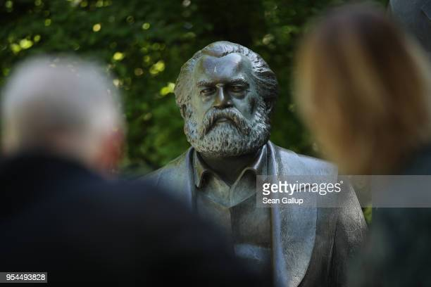 Visitors look at a statue of philosopher and revolutionary Karl Marx in a public park on May 4 2018 in Berlin Germany The German city of Trier Marx's...