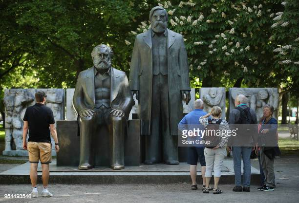 Visitors look at a statue of philosophers Karl Marx and Friedrich Engels in a public park on May 4 2018 in Berlin Germany The German city of Trier...