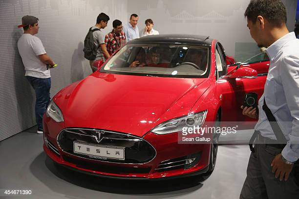 Visitors look at a Tesla Model S electric car at the Panasonic stand at the 2014 IFA home electronics and appliances trade fair on September 5 2014...