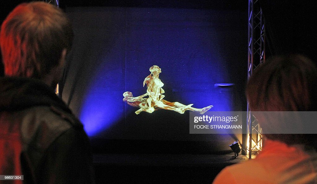 Visitors look at a three-dimensional hologram of a plastinated couple during the sexual act at the exhibition 'Koerperwelten - eine Herzenssache' (Body worlds - a heart issue) by German 'plastinator' Gunther von Hagens on April 23, 2010 in Bremen, northern Germany. The city of Bremen prohibited to show the original plastinate in the exhibition.
