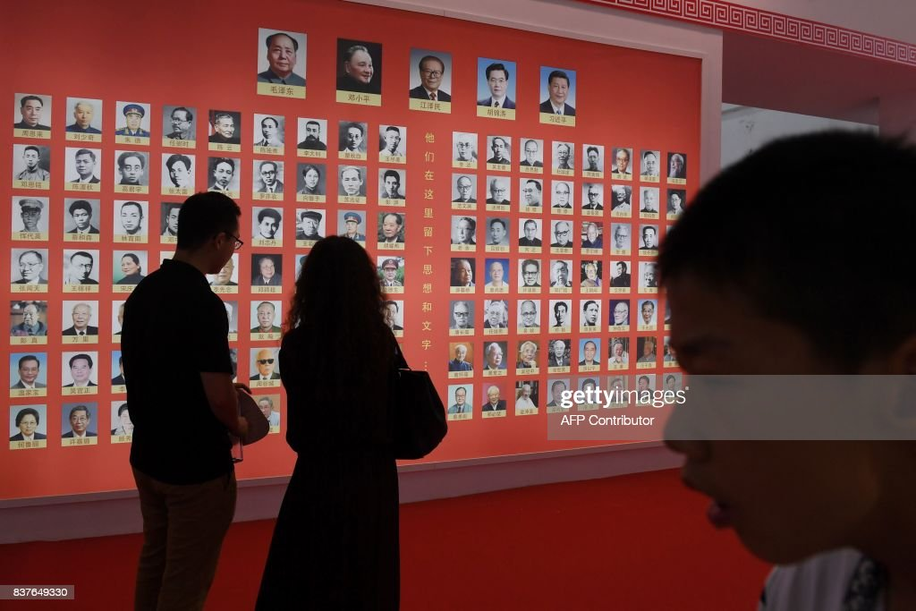 Visitors look at a wall display of photos of Chinese leaders at the Beijing International Book Fair in Beijing on August 23, 2017. The book fair runs from August 23 to 27. / AFP PHOTO / Greg Baker
