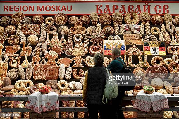 Visitors look at a wall with several typica russian breads at the russian stand at the Gruene Woche agricultural trade fair on January 17 2014 in...