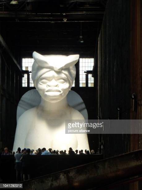 Visitors look at a white sphinx made of sugar by African American artist Kara Walker in the former Domino sugar factory in Williamsburg Brooklyn New...