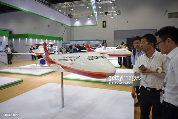 Visitors look at an ARJ21 model designed by the Commercial Aircraft Corporation of China at the Beijing International Aviation Expo in Beijing on...