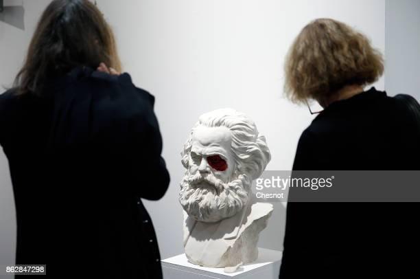 Visitors look at an artwork entitled 'Carlos Marx' by Cuban artist Lazaro Saavedra at the Grand Palais as part of the FIAC international contemporary...
