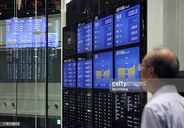 Visitors look at an electronic board displaying stock figures at the Tokyo Stock Exchange in Tokyo, Japan, on Wednesday, Aug. 28, 2013. Japanese...