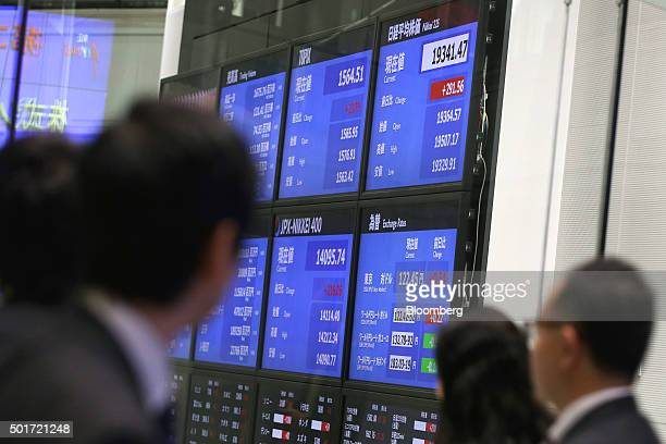 Visitors look at an electronic boards displaying market indices at the Tokyo Stock Exchange operated by Japan Exchange Group Inc in Tokyo Japan on...