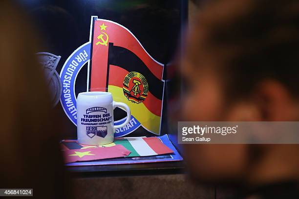 Visitors look at an exhibit that includes the Soviet and communist East German flags at the DDR Museum on October 8 2014 in Berlin Germany Germany...